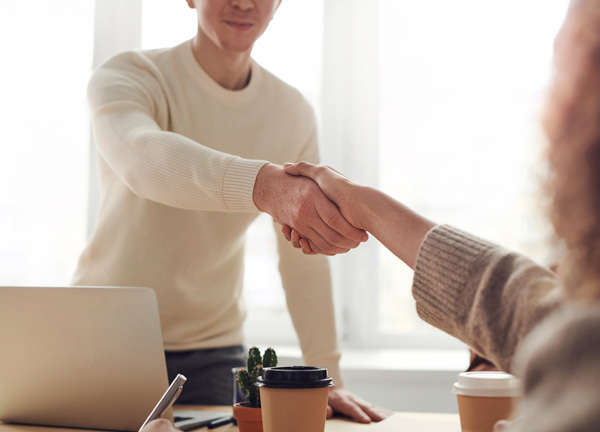 a man and a woman shaking hands in a business transaction.